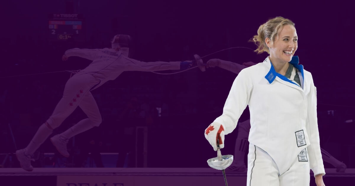 Sherraine Schalm wearing her fencing whites while holding her epee towards the floor. She is laughing